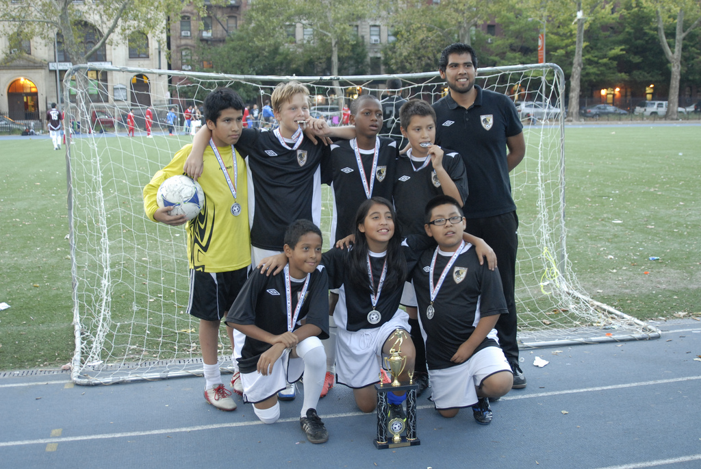 FC Harlem's U12 Team poses with the club's first trophy in tournament play.